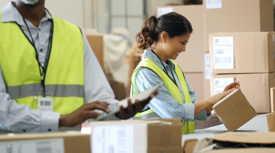 postal workers handling packages in facility